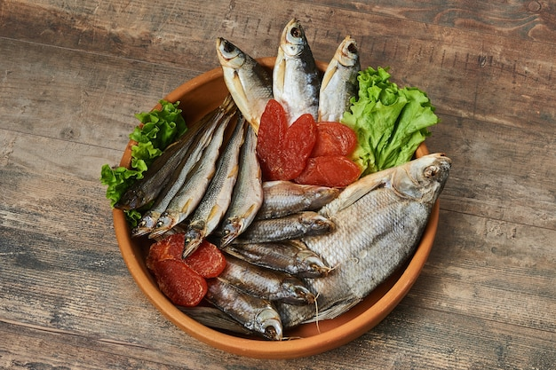 Salty stockfish on wooden table. rainbow smelt, common bream, vobla, shemay, macrourus caviar and lettuce leaves.
