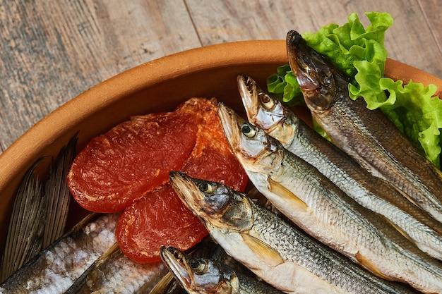 Salty stockfish on wooden table. rainbow smelt, vobla, macrourus caviar and lettuce leaves. Premium Photo