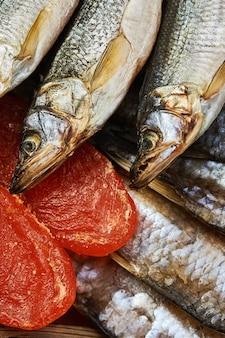 Salty stockfish on wooden table. rainbow smelt, vobla and macrourus caviar.