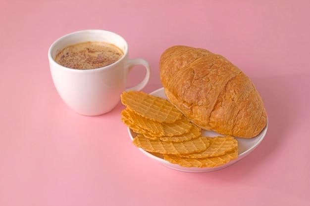 파스텔 핑크 배경에 거품 커피와 초콜릿 한 잔을 곁들인 짭짤한 와플과 달콤한 크루아상