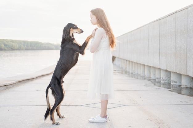 강둑 근처에 매력적인 젊은 여자와 함께 서 있는 saluki 개 초상화를 닫습니다