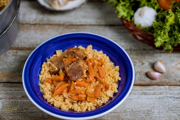 Samarkand pilaf lamb, rice, onion, yellow carrots, vegetable spices table in uzbek national dish.