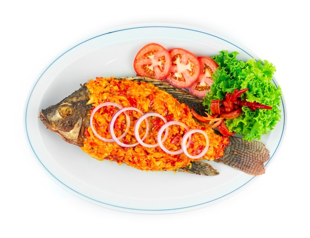 Sambal fish with hot chili paste sambal saucestyle popular condiment in malaysia, indonesia, and singapore decoration carved chili and vegetables topview