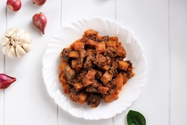 サンバルゴレンアティケンタンまたはホットスパイシーレバーアンドポテト、インドネシアの伝統的な料理、通常はケトゥパットまたはロントンとのイードアルフィトルのお祝いの間に提供されます。セラミックホワイトプレートでお召し上がりいただけます