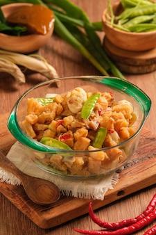 Sambal goreng kentang은 나무 테이블 위의 그릇에 제공됩니다. 튀긴 감자에 매운 조미료와 완두콩을 섞어 만든 인도네시아 전통 음식입니다. 이드 기간 동안 제공되는 특별 요리