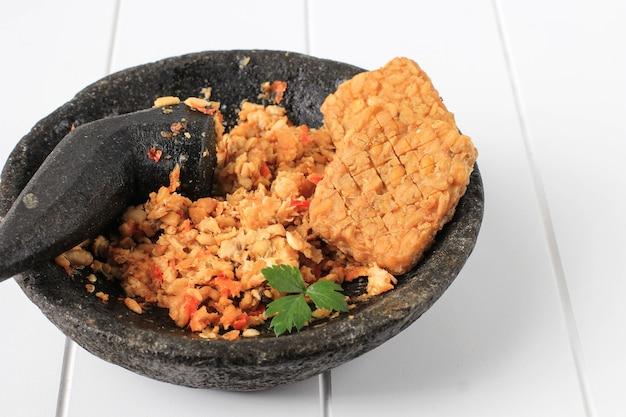 Sambal tempeh, пряный измельченный темпе на каменном пестике. традиционные индонезийские блюда с острым и пикантным вкусом. копирование пространства на белом фоне деревянные