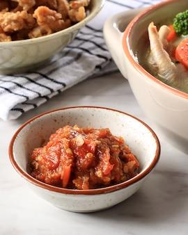 Sambal terasi, индонезийский традиционный соус чили с креветочной пастой, помидорами и чили, гарнир для ежедневного меню. подается на маленькой миске, на белом столе