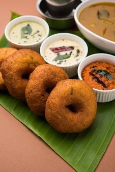 サンバーヴァーダまたはメドゥヴァーダ、不機嫌そうな背景の上に緑、赤、ココナッツのチャツネを添えた人気の南インド料理。セレクティブフォーカス