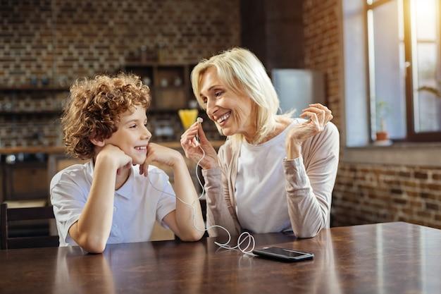 같은 음악 취향. 쾌활한 수석 여자는 그녀의 얼굴에 넓은 미소로 그녀의 손자를보고 그 옆에 앉아 집에서 이어폰에서 재생되는 음악에 대해 이야기합니다.