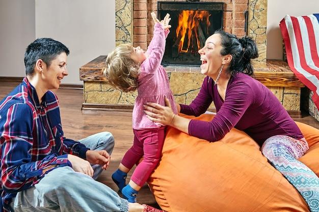 동성 커플과 그들의 작은 딸이 벽난로 근처에서 놀고있는 콩 주머니 의자에 앉아있다.