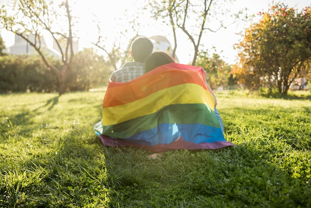 Same-sex couple in lgbt flag sitting in park