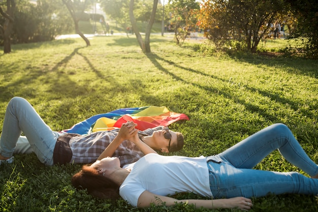Same-sex couple lying in park