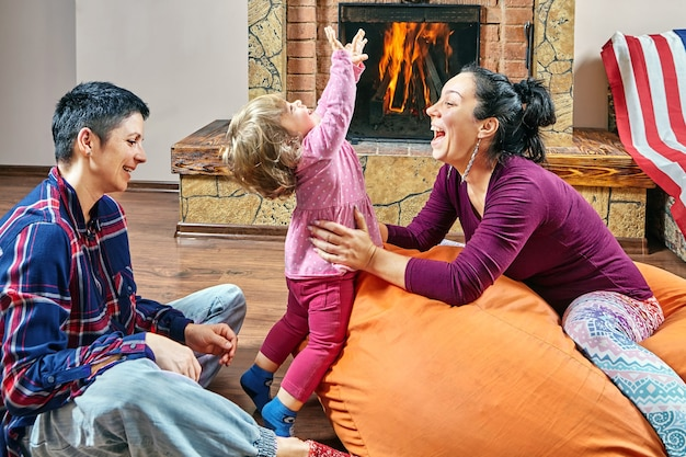 Same sex couple and their little daughter are sitting on bean bag chair, playing near fireplace.