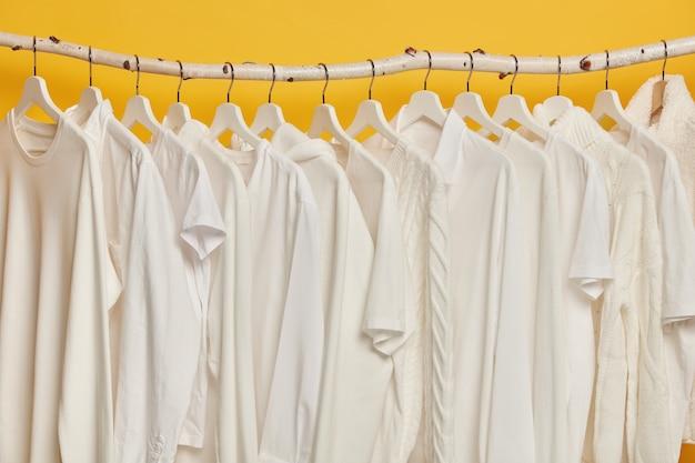 Stessi vestiti bianchi su scaffalature di legno nell'armadio. collezione di abbigliamento su grucce, isolato su sfondo giallo.