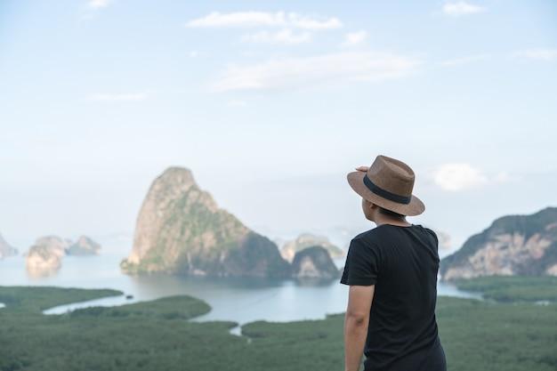 Samed nang chee. man with view of the phang nga bay, mangrove tree forest and hills at andaman sea, thailand.