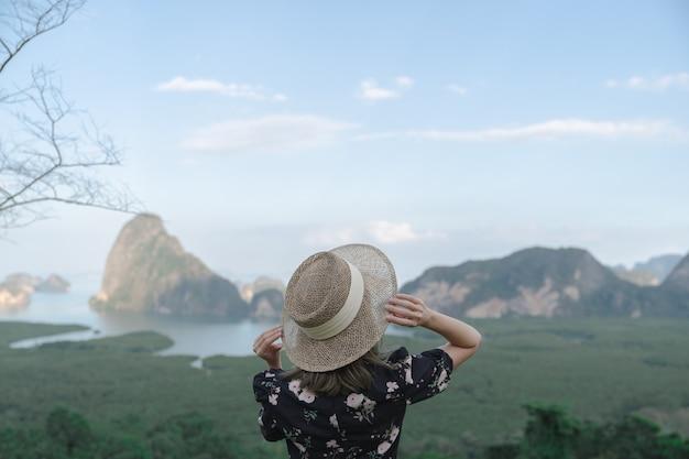 Samed nang chee. woman with view of the phang nga bay, mangrove tree forest and hills at andaman sea, thailand.