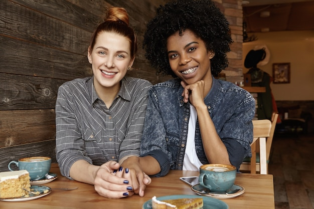 Samesex homosexual female partners drinking coffee and eating cakes at restaurant
