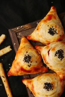 Samosa, samsa 고기 박제 파이, 오리엔탈 스타일. 나무와 검은 테이블 상단보기에 우즈베키스탄 국가 요리 samosa