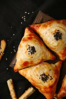 Samosa, Samsa 고기 박제 파이, 오리엔탈 스타일. 나무와 검은 테이블 상단보기에 우즈베키스탄 국가 요리 Samosa 프리미엄 사진