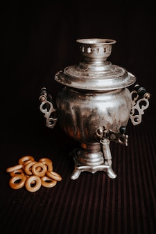 Samovar or russian boiling tank with cracknels on the brown background