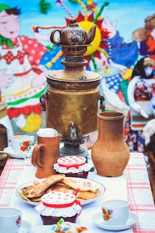 Samovar on the table next to rustic dishes