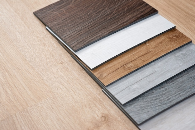 Пример каталога роскошных виниловых напольных плиток с новым дизайном интерьера для дома или пола на светлом деревянном столе.