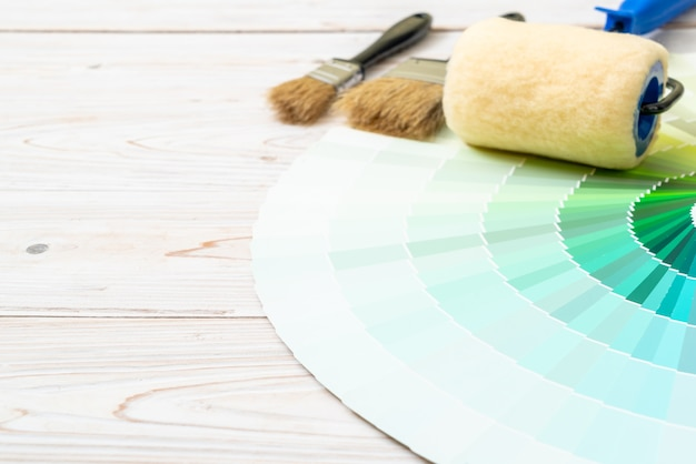 Sample colors catalogue or colour swatches book with paint roller brush