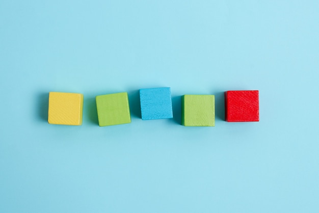 Прямоугольные коробки с образцом куба, отполированные разноцветными цветами, символизирующими развитие стабильности, выровненные по поверхности с разной перспективой, ограниченные аксессуарами для электронных расходных материалов