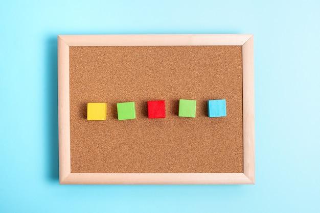 Прямоугольные коробки с образцом куба, отполированные разноцветными цветами, символизирующими развитие устойчивости, выровненные по поверхности с разной перспективой, ограниченные аксессуарами для электронных товаров