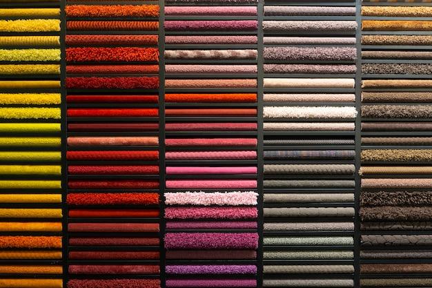 Образцы ковров разных цветов на стенде в магазине или производстве. образцы разноцветных ковров на полу Premium Фотографии