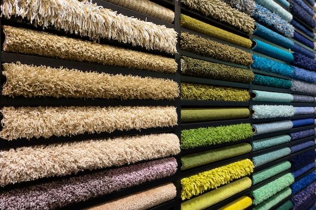 Образцы ковров разных цветов на стенде в магазине или производстве. образцы разноцветных ковров на полу