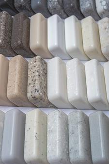 天然花崗岩、大理石、石英石、カウンタートップのサンプル。石からのモデル、クローズアップ。天然石で作られたモダンな色のスラブ。