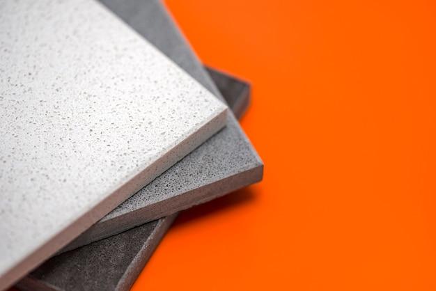 キッチンカウンターや床タイル用の天然石のサンプル。オレンジ色の背景のカウンタートップの石のサンプル、デザインやテキストのコピースペース。