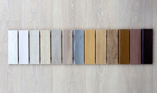 라미네이트 및 쪽모이 세공 마루를위한 다양한 색상 및 종류의 목재 샘플. 바닥 및 스커트 보드 생산을위한 다색 목재 샘플