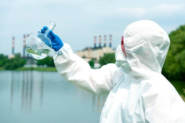 개방 수역에서 샘플링. 과학자나 생물학자는 산업 공장 근처에서 물 샘플을 채취합니다. 둥근 화학 플라스크에 담긴 물 샘플.