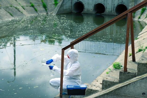 개방 수역에서 샘플링. 과학자나 생물학자가 산업 공장 근처에서 물 샘플을 채취합니다. 피펫이 있는 화학 시험관의 물 샘플.