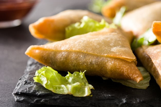 Samsa or samosas with meat and vegetables on black background. traditional indian food.close up