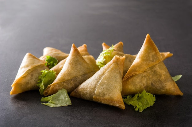 Samsa or samosas with meat and vegetables on black. traditional indian food.