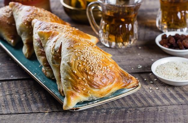 東洋料理。肉、木製のテーブルにお茶のグラスとおいしいサモサsamsa。ラマダン料理