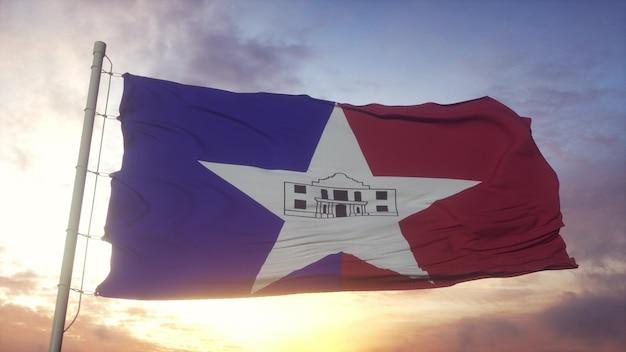 風、空、太陽の背景に手を振っているテキサス州サンアントニオ市の旗。 3dレンダリング