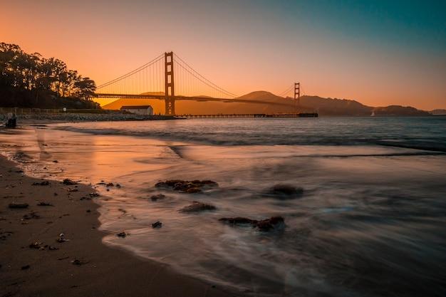 サンフランシスコ、カリフォルニア州アメリカ合衆国。サンフランシスコのゴールデンゲートの赤い夕日にビーチから長時間露光