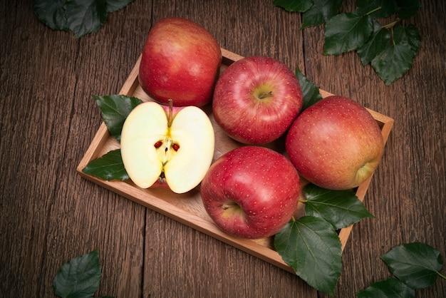 정원에 있는 나무 테이블에 있는 나무 바구니에 있는 산 후지 사과 또는 분홍색 사과