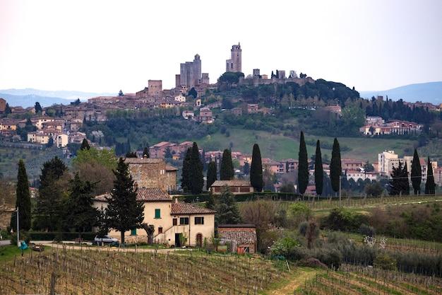 サンジミニャーノ。典型的なトスカーナの風景-丘の上の別荘、ヒノキの路地、ブドウ園のある谷、シエナ県の景色。イタリア、トスカーナ