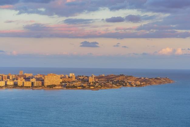 Вид на сан-хуан и кабо-лас-уэртас из замка санта-барбара. средиземное море спокойное, а небо затягивается облаками.
