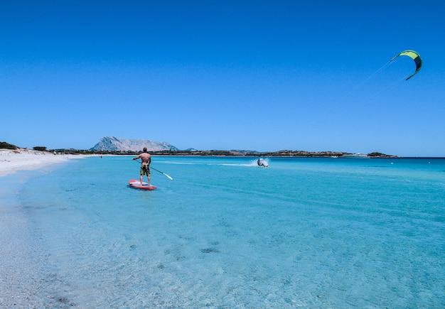 Сан теодоро - пляж ла синта - июль 2017 года - юный спортсмен веслом на вертикальном весле в кристально чистом море сардинии, в то время как кайтсерфер скользит по воде рядом с ним