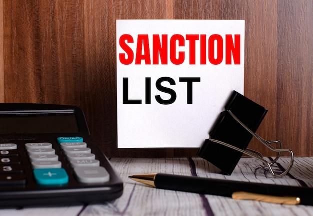 Sanction list is written on a white card on a wooden table next to a calculator and pen.