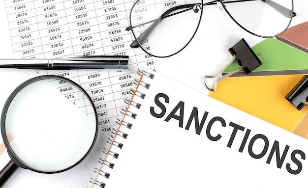 Санкции - надпись текста на блокноте и графике.
