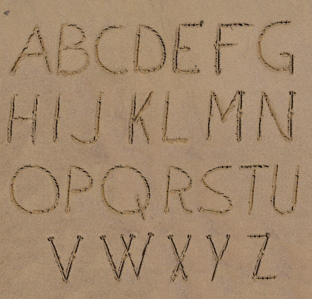해변에 손으로 쓴 모래 알파벳 편지