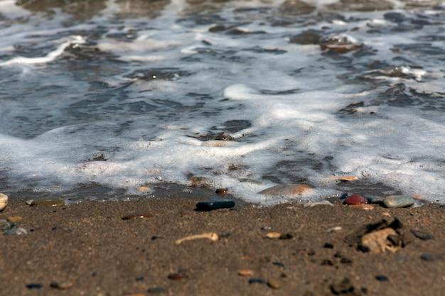 Берег песчано-галечного пляжа, залитый пеной волны, крупным планом с деталями и текстурами