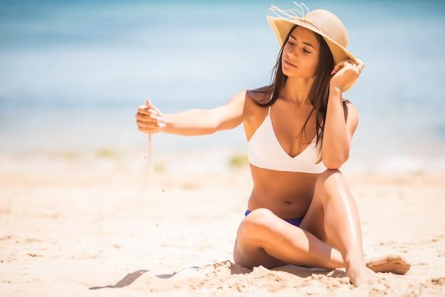時があなたの指をすり抜けるように砂をまいてください。砂の海の背景を保持している女の子。暖かい気候、海への旅での休暇の概念